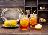 Iced tea with lemon on a rustic wooden background