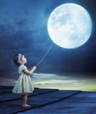 Conceptual image of a baby holding a moon-balloon
