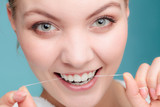 Woman face smiling with dental floss.