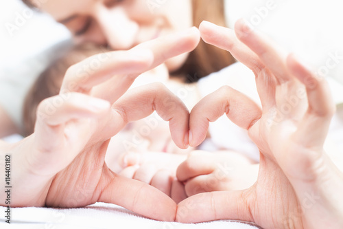 fototapeta na ścianę Happy mother and baby. Heart symbol by hands. Family care