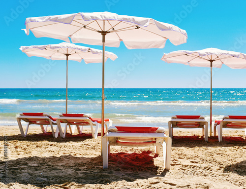 sunloungers and umbrellas in a quiet beach Poster