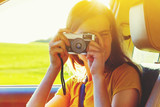 girl taking photo with camera moving in car