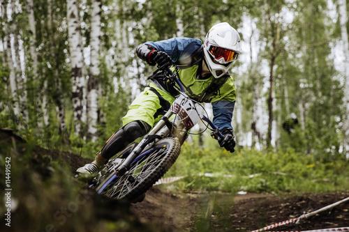 closeup man athlete mountain biking around sharp turn in forest during competition downhill