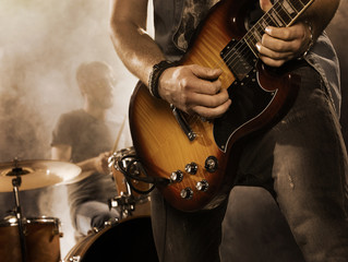 Rock band performs on stage. Guitarist.