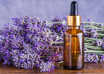 Lavender oil bottle on wood background.Essential oil, natural remedies.