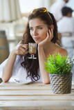 Portrait of beautiful blond woman sitting in outdoors cafe in It