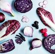 Various cut purple,red fruits and vegetables on light blue background.