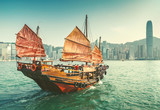 Scenic view over Hong-kong skyscprapers and a junkboat sailing. Iconic landmark of Hong-Kong.