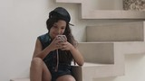 Girl sitting on steps and playing with mobile phone