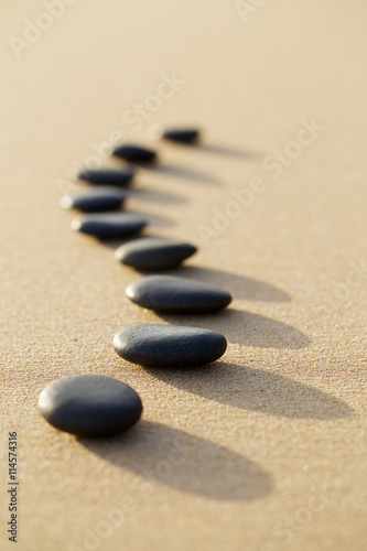 Foto op Canvas Zen set of hot stone on white sand calm beach in backbone shape. sel