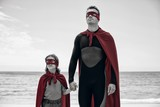 Father and daughter in superhero costume sea shore
