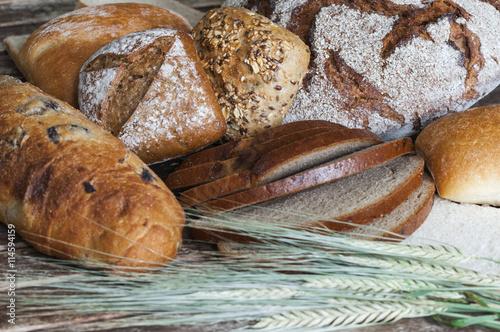 fototapeta na ścianę Verschiedene Brotsorten auf einem Holztisch / Verschiedene Brotsorten mit Getreideaehren auf einem Holztisch.