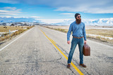 bearded hipster hitch hiker standing in middle of road in nevada with suit case