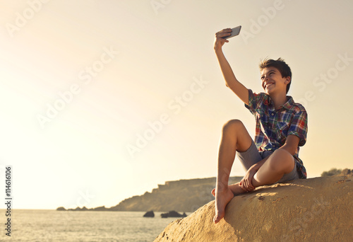 mata magnetyczna Young boy doing a selfie at the beach