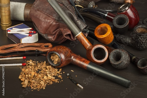 Old tobacco pipe and spilled tobacco, used on a black wooden background Poster