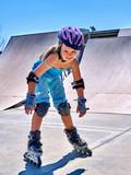 Child riding on roller skates in skatepark. Child in protection for skates