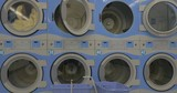 Fee-paying laundry service. Two rows of big washing machines with linen washed in the one