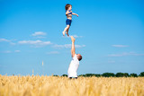 father tosses child in a wheat field