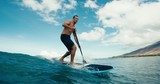 Surfer riding blue ocean wave stand up paddle boarding