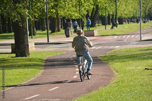 anciano circulando en bicicleta por la ciudad