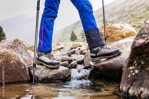 Poster Waterproof trekking boots wade a rocky mountain stream