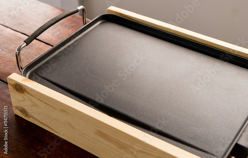 Poster Empty Electrical cooking pan on wooden table