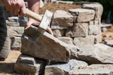 Maurer beim Behauen von Naturstein