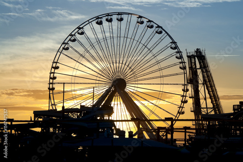 Fotobehang Amusementspark Ferris Wheel and roller coaster silhouette at sunset. Taken in Wildwood, New Jersey