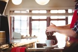 Mid section of waiter pouring a cup of coffee