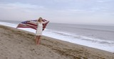 Beautiful young blonde woman in a white dress skips along a California beach, letting a big United States flag fly behind her.  Wide shot, recorded hand held in slow motion.