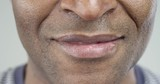 Extreme Close-Up of a Smile of an Afro-American Man/Slow motion of a smiling African American. Only the lower part of the face In the frame. His smile is wide and happy