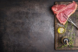Fototapety Raw T-bone Steak for grill or BBQ with meat fork and flavoring on aged cutting board and dark rustic metal background, top view, border