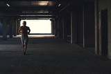 Male athlete running on industrial building, fitness