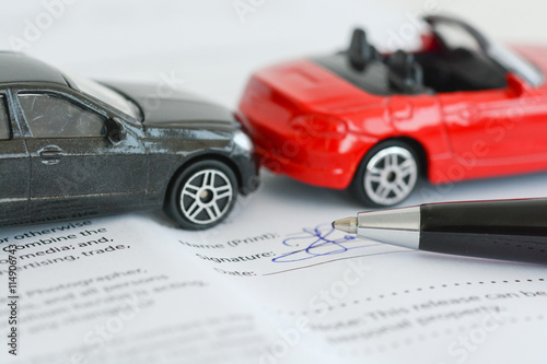 Insurance policy contract concept with toy model cars having a crash or accident  - 114906743