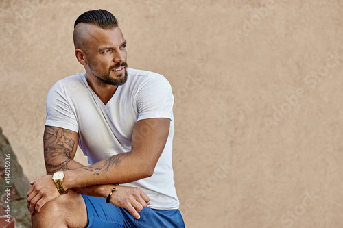 fototapeta na ścianę Tattooed brutal man with arms folded wearing white t-shirt - cop