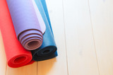 Different color  mats for yoga, fitness or pilates on wooden background with copy space.