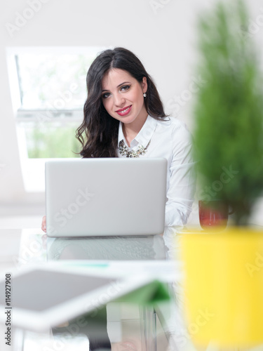Fotobehang Beautiful brunette woman doingwork in her office with greenery.