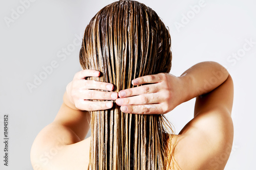 Woman applying hair conditioner. Isolated on white. Plakat