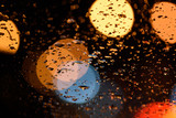Abstract raindrops on glass and lights on the road, soft focus.