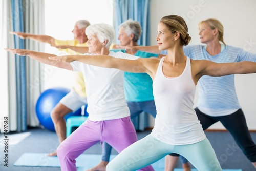 Instructor performing yoga with seniors плакат