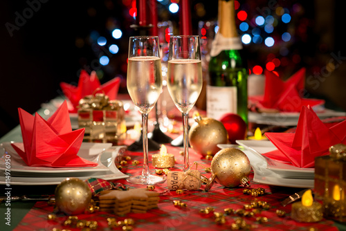 Zdjęcia na płótnie, fototapety, obrazy : christmas eve party table with champagne flute with red and golden glitter