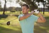 Handsome golfer man taking shot