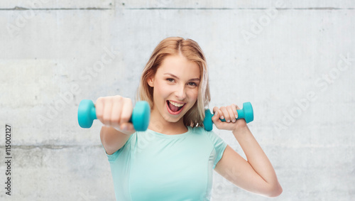 obraz lub plakat smiling beautiful young sporty woman with dumbbell