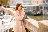 Young woman enjoying coffee with chocolate cake near the river in the center of Ljubljana city. Traveling Slovenia