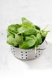 Fresh clean spinach in a metal colander, vertical