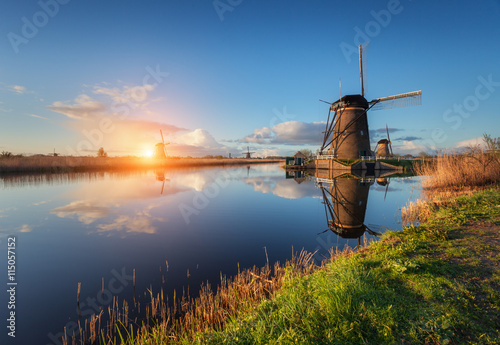 obraz lub plakat Beautiful traditional dutch windmills near the water channels with reflection in water at colorful sunrise in famous Kinderdijk, Netherlands