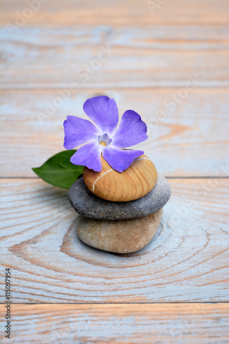 Three cairn natural Zen stones piled up on a old brown gray wooden background wi Poster