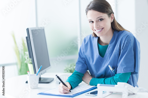 Female doctor at the reception desk плакат