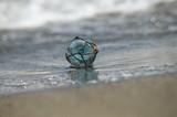 波打ち際の小さなガラスの浮き球