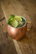 Moscow mule cocktail with ginger, lime and mint sprigs in a copper mug on wooden surface